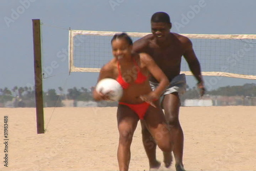 Young African American couple playing volleyball at the beach