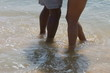 Young African American couple with feet in sand at beachside