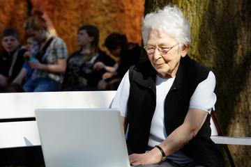 Nette alte Dame mit Laptop auf Bank 29