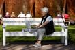 Nette alte Dame mit Laptop auf Bank 21