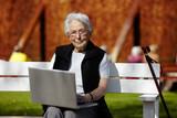 Nette alte Dame mit Laptop auf Bank 16