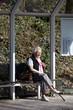 Nette alte Dame in Bushaltestelle