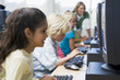 Children at computer terminals with teacher in background
