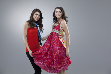 happy two women trying red flower dress