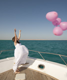 Bride releasing balloons from a boat poster
