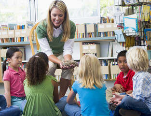 Kindergarten teacher and children looking at bird's nest in libr