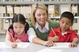 Fototapety Kindergarten teacher helping students with writing skills