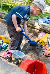 Junge schaufelt Sand auf Laster