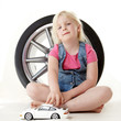 Cute blond girl playing with a toy car in front of a tyre