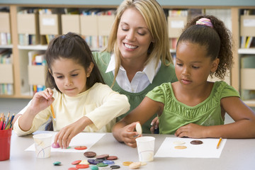 Kindergarten teacher sitting with students in art class,