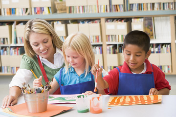 Kindergarten teacher sitting with students in art class