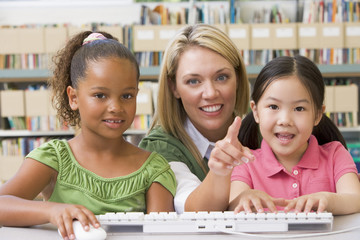 Kindergarten teacher sitting with children at computer