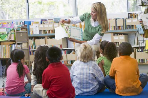 Kindergarten teacher reading to children in library - 31998022