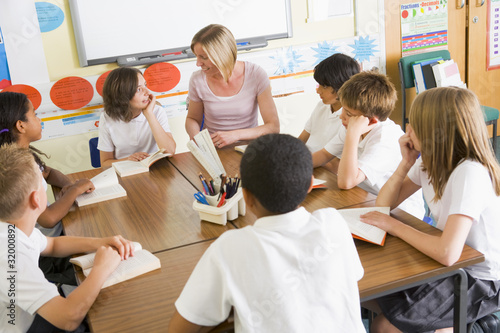 Schoolchildren and their teacher reading books in class