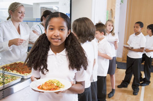 Schoolgirl holding plate of lunch in school cafeteria