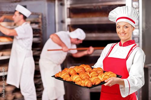 Female baker holding freshly baked croissants in bakery