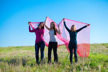 three young beautiful woman standing with tissue into the field