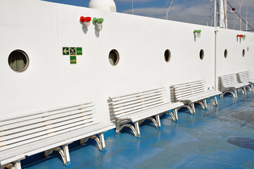 benches and portholes on ship deck