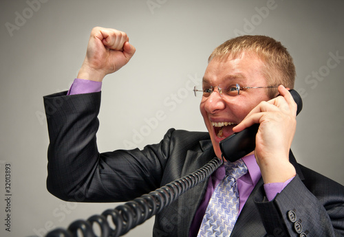 Happy businessman talking by phone