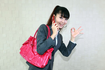 電話をしながらOKサインをしている笑顔の女性