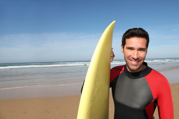 Portrait of young man with surfboard