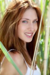 Portrait of beautiful woman in reeds field