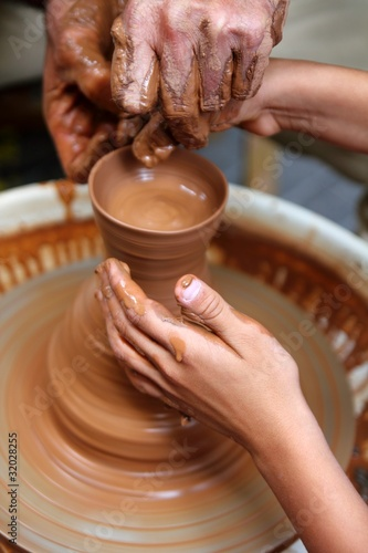 craftsman potter hands of teacher and pupil clay pottery