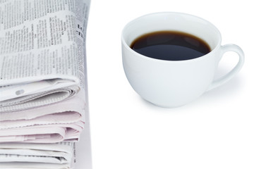 Stack of newspapers and cup of coffee