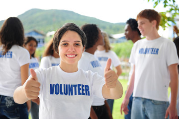 happy volunteer girl showing thumbs up sign