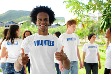 happy volunteer african american man showing thumbs up sign