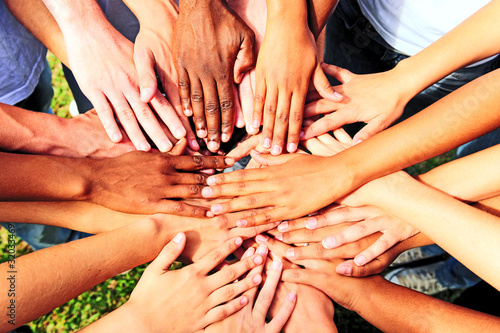 Leinwanddruck Bild many hands together: group of people joining hands