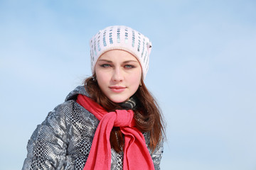 Portrait of girl in winter clothes and by  red scarf