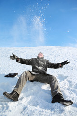 Young man sitting on snow and throw him upwards