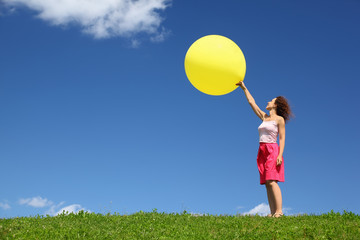 Woman stands in summer on grass and starts inflatable ball