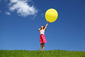Woman stands in summer in field holds  balloon and looks in sky