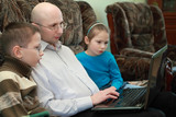 Father, son and daughter sitting on couch and look at laptop