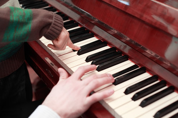 hands of a father and son playing on brown piano