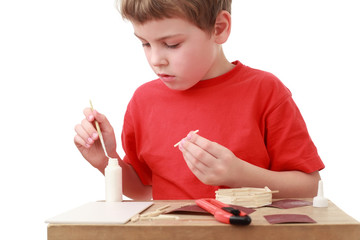 little boy in red T-shirt crafts at small table