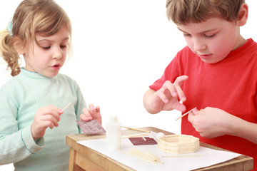 little girl and boy in red T-shirt crafts at small table