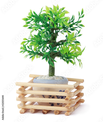 small beautiful toy green tree in pot, wooden sticks