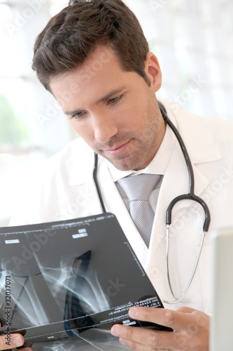 Portrait of young doctor checking X-Ray
