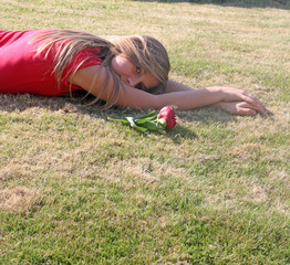 beautiful girl laying down with flower by her side