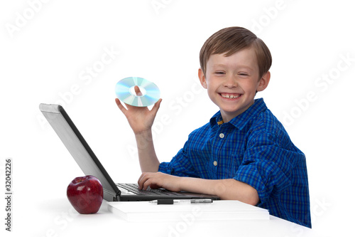 Young caucasian boy working on laptop with a CD