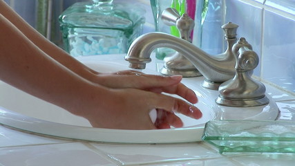 Woman washing hands in the sink