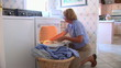 Mature woman removing clothes from dryer