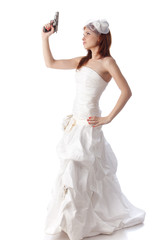 Young woman in a wedding dress with gun.