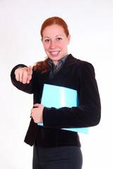 Девушка в пиджаке, с папкой в руках указывает пальцем