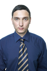 Serious young man in dark blue shirt and tie isolated on white