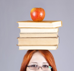 Redhead girl keep apple and books on her head.
