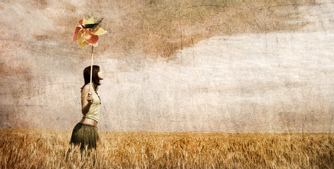 Girl with wind turbine at wheat field. Photo in old color image
